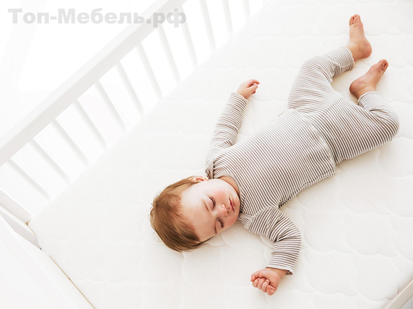 Ребенок в кроватке на матрасе
