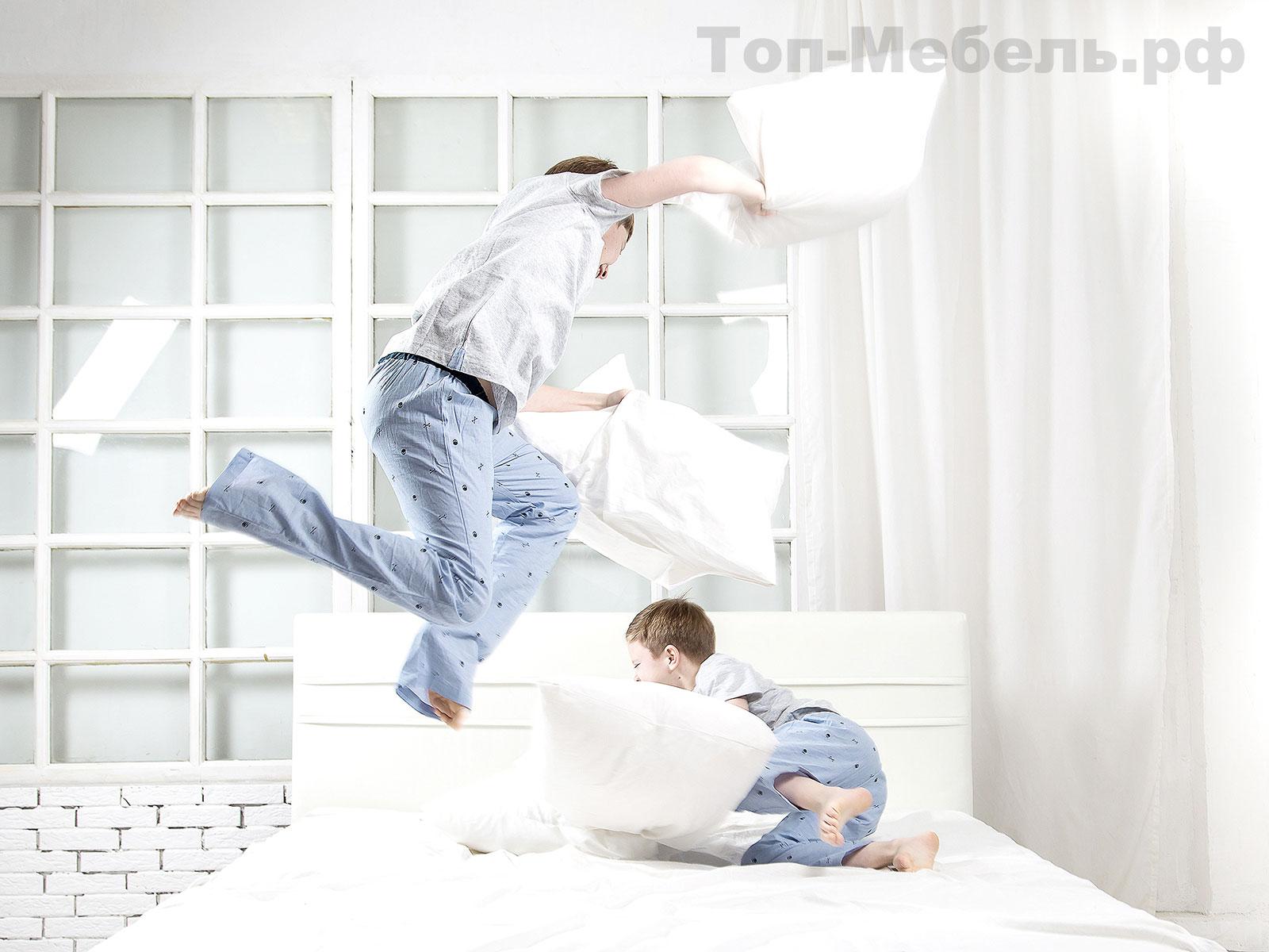 Дети на кровати играют с подушками