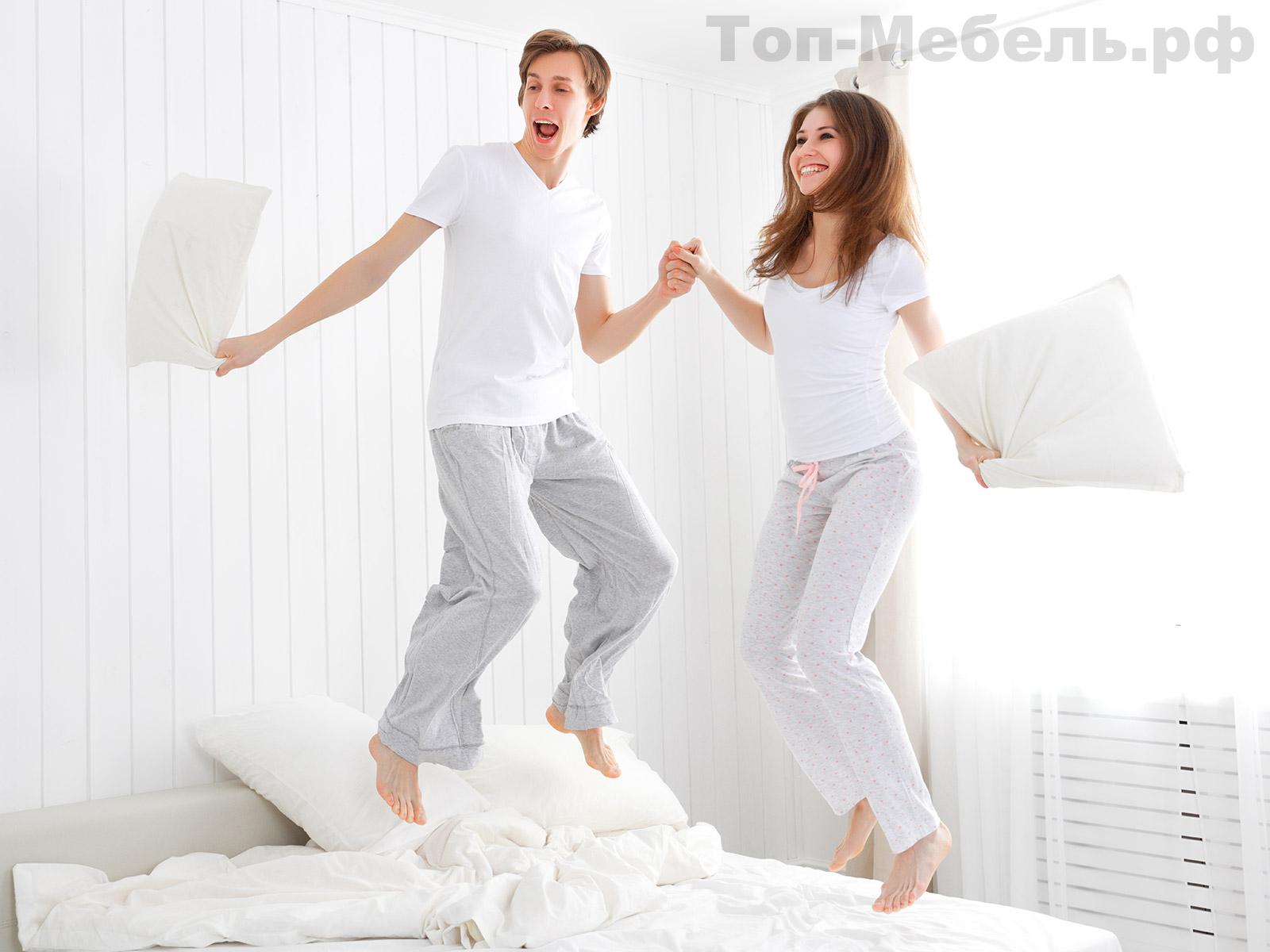 Юноша и девушка прыгают на кровати